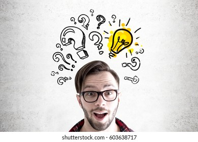 Close up of a head of a hipster guy standing near a concrete wall with a light bulb surrounded by question marks.