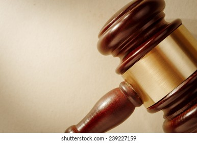 Close up of the head of a judge or auctioneers wooden gavel with a brass band around it and copyspace