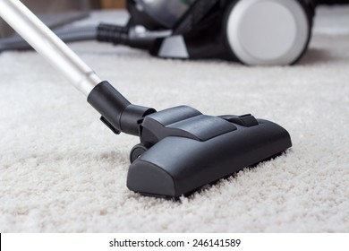 Close up of the head of a modern vacuum cleaner being used while vacuuming a thick pile white carpet