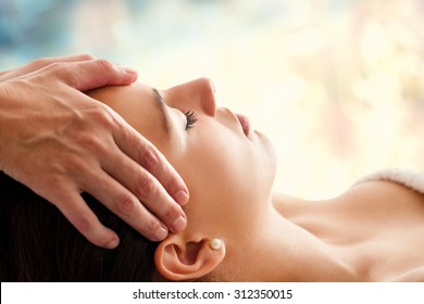 Close up head portrait of young woman having facial massage in spa. Therapist doing head massage  against colorful background.