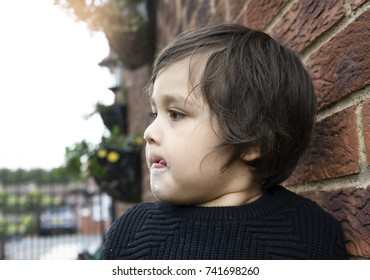 Close up head shot of Active little boy  standing next to wall brick and licking his lips after finished eating sweet cotton candy, Unhealthy food concept