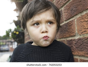 Close up head shot of Active little boy  standing next to wall brick and making funny face after finished eating sweet cotton candy, Unhealthy food concept
