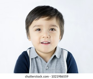 Close up head shot of adorable boy looking at camera with smiling face on isolated white background, Portrait of Happy child with smile mouth and beautiful brown eyes looking up, Healthy children