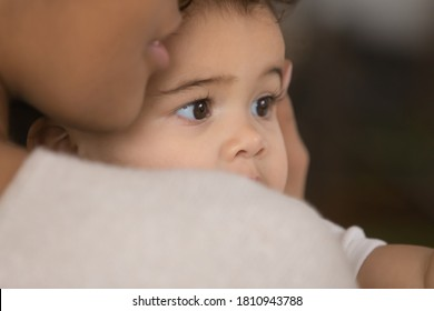 Close up head shot affectionate african american woman cuddling sweet funny little biracial baby boy or girl, expressing warm loving caring feeling. Childhood custody foster, family relations concept