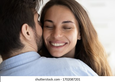 Close up head shot affectionate loving man cuddling beautiful young mixed race woman, whispering sweet words in ear. Caring husband showing love to bonding attractive wife, enjoying tender moment.