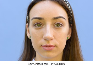 Close up head shot of an attractive young brunette woman with green eyes posing over a blue background