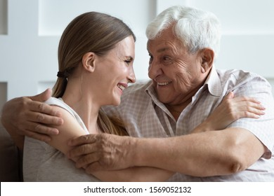 Close up head shot bonding two generations family embracing, enjoying sweet tender moment at home. Happy young woman communicating, chatting with pleasant smiling 70s father, sitting on couch.