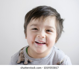 Close up head shot happy child with a big smiling face on white background, Adorable Kid boy in pajamas looking up at camera with a happy face after wake up in the morning, Healthy children concept