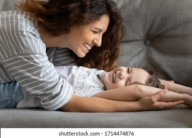 Close up head shot joyful young mom having fun with small child daughter, lying on cozy couch. Smiling affectionate two female generations family enjoying playtime together on comfortable sofa.