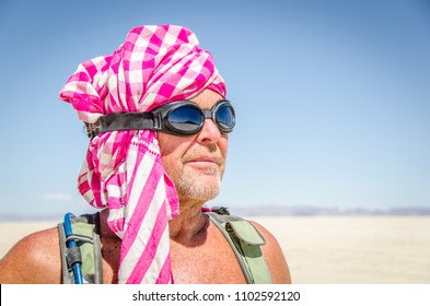 Close up head shot of man in pink and white headdress and goggles at burning man