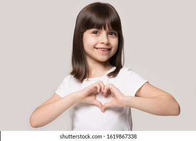 Close up head shot portrait happy cute preschool girl making heart gesture, isolated on grey pastel studio background. Smiling brown-haired 6 years old charming satisfied cutie showing love sign.