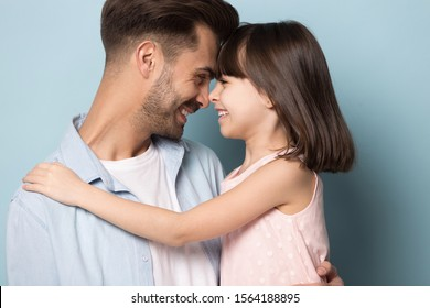 Close up head shot portrait image with smiling parent and little brown-haired girl. Concept happy father and daughter embracing and facial touch on blue background, six year child and middle age man