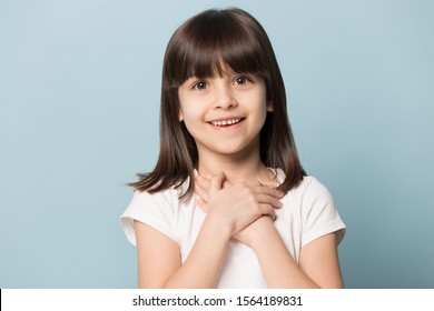 Close up head shot portrait image with smiling and cute little brown-haired girl. Concept happy kid lovely hold abstract heart on blue background, six year child looking at camera and gesture