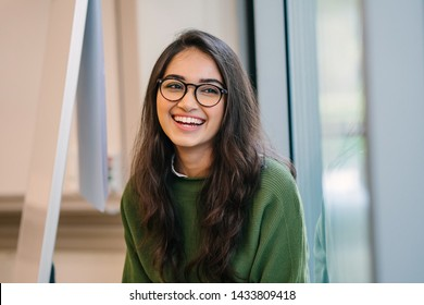 A close up head shot portrait of a preppy, young, beautiful, confident and attractive Indian Asian woman in a green sweater and spectacles in a classroom or office. She is smiling happily.