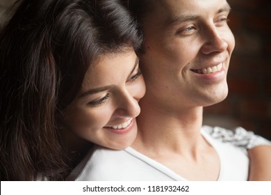 Close up head shot portrait of smiling happy young man and woman hugging and looking away. Attractive affectionate couple in love, romantic relationship and just a married concept