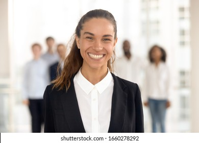 Close up head shot portrait smiling mixed race businesswoman in office. Happy diverse attractive female employee ceo looking at camera, headshot confident successful woman boss or manager at work.