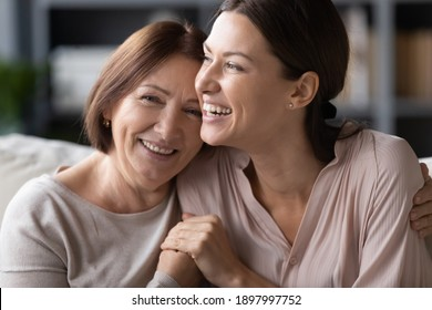 Close up head shot portrait smiling mature mother and grownup daughter cuddling, family enjoying tender moment, happy young woman with elderly mum hugging, spending leisure time together - Shutterstock ID 1897997752