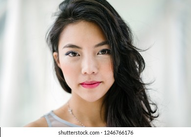 A close up head shot portrait of a young, beautiful and unique Chinese Asian woman. The model has full lips and large eyes. She is smiling as she gazes into the camera.