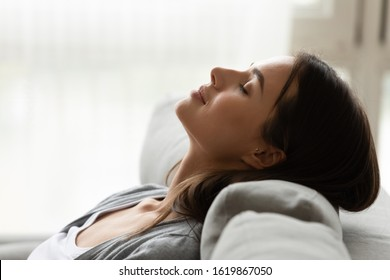 Close up head shot profile peaceful beautiful woman relaxing, sleeping on comfortable couch at home, pretty young female enjoying rest, weekend, breathing fresh air, meditating with closed eyes