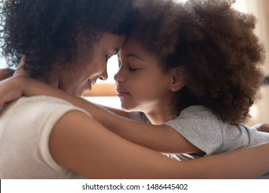 Close up head shot side view calm happy mixed race mother cuddling little cute daughter, touching foreheads. Tender moment family support, forgive and understanding. Adopted kid hugging foster mom.