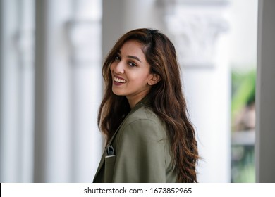 Close up head shot of a young, beautiful, confident, sexy and attractive Indian woman in a white tee with a green jacket over her shoulders. She is smiling naturally as she looks at the camera.