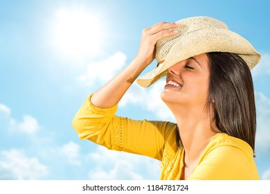 Close up head shot of young carefree woman laughing outdoors. Happy girl in yellow dress holding hat against blue sunny sky.