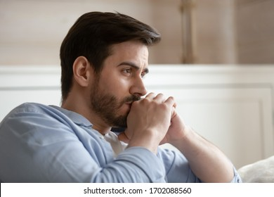 Close up head shot young thoughtful man looking away. Pensive millennial bearded guy thinking of problems, feeling stressed, sitting alone on couch at home, worrying about personal troubles.