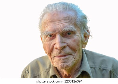 Close up head and shoulders of a distinguished elderly man looking at the camera with a quiet smile against white background