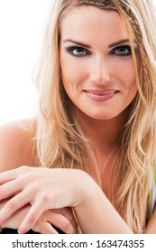 Close up head and shoulders portrait on white of a beautiful woman with long blond hair sitting smiling at the camera with her hands folded in front of her
