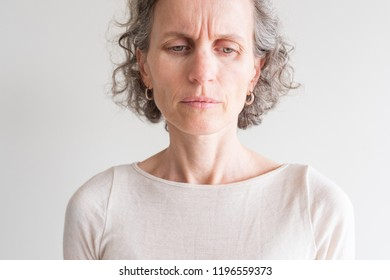 Close up head and shoulders view of middle aged woman with grey hair and cream top frowning and showing wrinkles (selective focus)