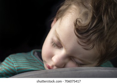 Close up of head and shoulders of young boy aged 2 to 3 years who has fallen asleep on a pillow in front of him whilst in an upright position.