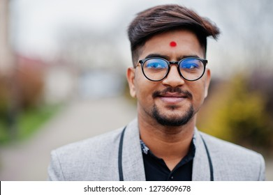 Close up head of stylish indian man with bindi on forehead and glasses, wear on suit posed outdoor.