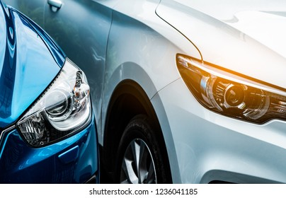 Close up headlamp light of blue and white SUV car. Blue car parked beside white car. Automotive industry concept. Electric or hybrid auto concept. Car service. Road trip adventure. Automobile rental.