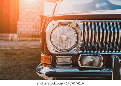Close up of headlight of custom tuned classic retro lowrider car in sunlight, toned