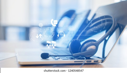 close up headphone of call center with telephone answer machine on table at operation room with virtual circle wheel business technology interface for telecommunication engineering concept