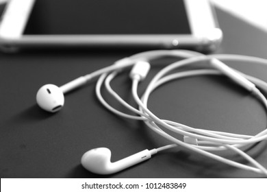 Close up headphone lay next to phone black and white