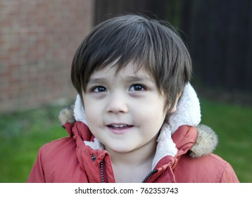 Close up head-shot of adorable little boy looking at camera with beautiful eyes, Kid boy portrait