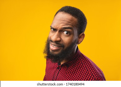 Close up headshot of confused african american man looking at camera with raised eyebrow, yellow studio wall