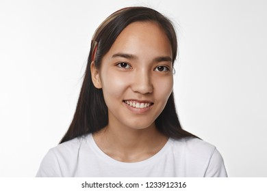 Close up headshot of joyful pleased beautiful young Asian female in white top smiling happily, rejoicing at good positive news, posing isolated against blank copyspace studio wall background
