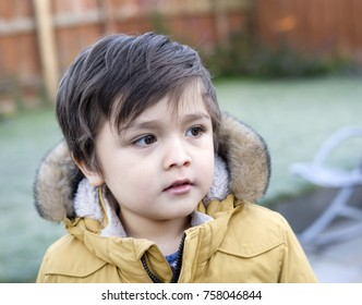 Close up headshot of Joyfull little boy with beautiful eyes looking out with thinking face with blurry background,Portrait  Kid boy hair style