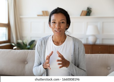 Close up headshot portrait of focused African American young woman sit on couch talk on video call, biracial millennial female rest on sofa at home have web conversation, shooting tutorial