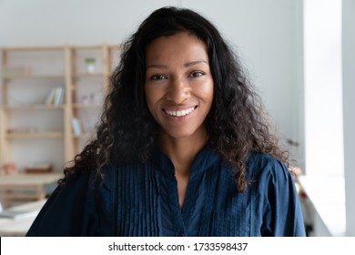 Close up headshot portrait picture of smiling african american businesswoman. Happy attractive confident young diverse woman mentor looking at camera on workplace background in coworking office.