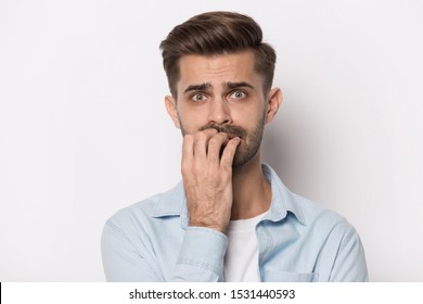 Close up headshot portrait of scared millennial caucasian man isolated on grey studio background bite nails feel frightened, anxious worried young male look terrified afraid, panic attack concept