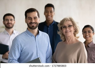 Close up headshot portrait of two happy businessman and mature businesswoman looking at camera. Diverse smiling employee standing behind of female and male company mentors. Leader of multi-ethnic team