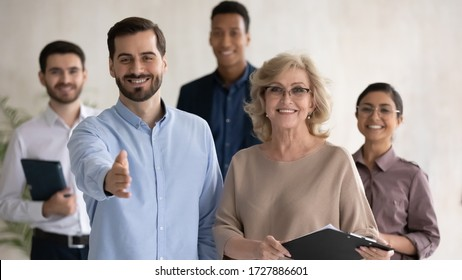 Close up headshot portrait of two happy businessman shaking hand posture and mature businesswoman looking at camera. Diverse smiling employee standing behind of male and female company mentors.