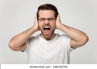 Close up headshot studio portrait young stressed mad man covering ears with hands, refusing to listen, suffering from loud noisy sounds, screaming, shouting, isolated on grey white background.