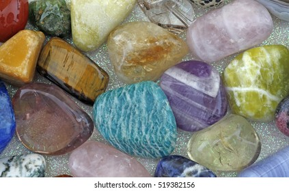 Close up of Healing Crystals - Various tumbled stones on an iridescent background including amazonite, ametrine, rose quartz, emerald, smokey quartz, citrine, jasper and tigers eye