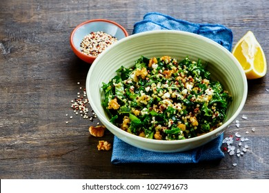Close up of healthy detox salad bowl on wooden background. Raw kale and quinoa salad with feta cheese and walnut. Side view. Clean eating, dieting, vegetarian food concept