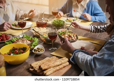 Close up of healthy food lying on dinner table. Elderly couple and father with kid are sitting together and eating wholesome dishes including salads, vegetables, meat, olives and wine