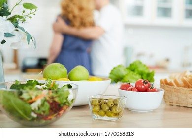 Close up of healthy food and snacks on kitchen counter with blurred silhouette of couple cooking in background, copy space